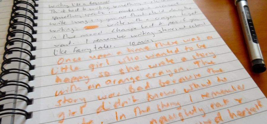 Writing with orange crayon